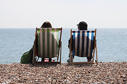 © Licensed to London News Pictures.04/05/2014. Brighton, UK. 2 people relaxing in a beach chair watching the sea. Thousands of people are visiting Brighton during the May bank holiday weekend. Photo credit : Hugo Michiels. Photo credit : Hugo Michiels