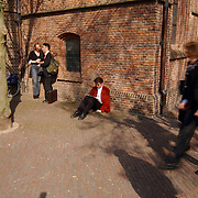 Matthaus Passion 2003, eenzaam wachtend de krant lezen in een voorjaarszon tegen een kerkmuur