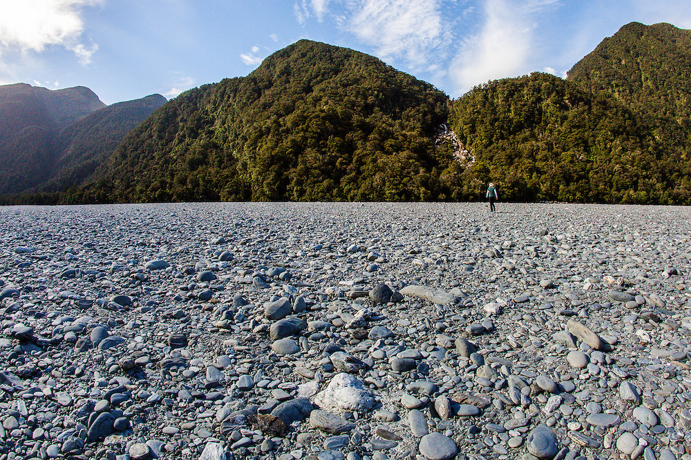 Cindy walks to a small waterfall across a dry riverbed resembling a moonscape.