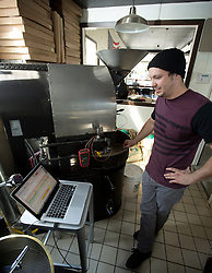 Devout Coffee co-owner and chief roaster Stevie Pape uses a laptop computer to monitor the roasting process as he prepares a 10-pound batch of Ethiopian coffee beans, Tuesday, April 5, 2016, in Fremont, Calif. (Photo by D. Ross Cameron)