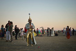 Apr 30, 2016 - Tankwa Town, Karoo Desert, South Africa - A man dressed up in costume stands among AfrikaBurn's many other participants during sunset on the Karoo Desert, South Africa, on April 30, 2016. A couple dressed up as bride and groom walk among the many sculptures at this year's AfrikaBurn in the Karoo Desert, South Africa, on April 30, 2016. AfrikaBurn, the smaller cousin of Burning Man, is now in its tenth year and aims to bring together creatives from all around the world to create art, exist in a non-monetary economy, and celebrate an alternative form of living. (Credit Image: © Tobin Jones/ZUMA Wire/ZUMAPRESS.com)