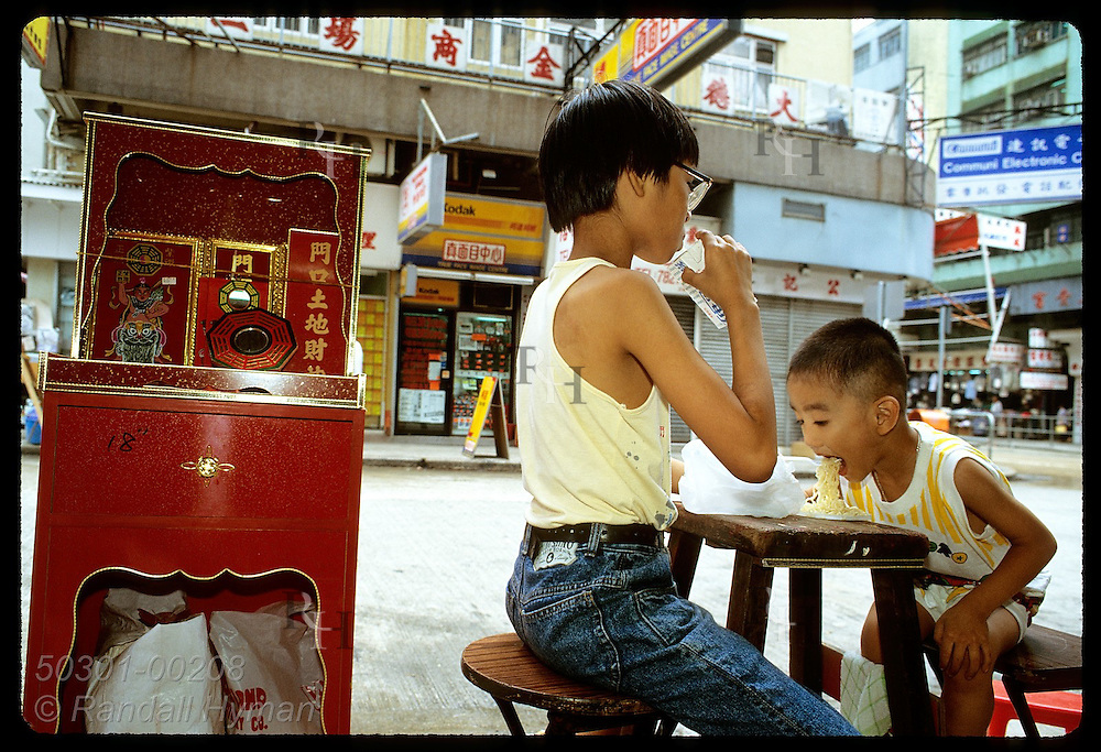 Boys eat noodle lunch on sidewalk outside mom's religious shop in Kowloon's Yau Ma Tei district Hong Kong