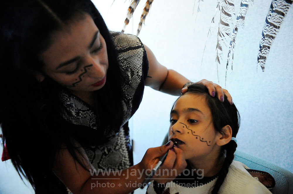 """Ehecatl Chantico Moreno (Wind and Fire of the Home) applies makeup to her daughter before a performance on September 9th, 2012 at Fiesta del Mar at the Monterey Bay Aquarium. By teaching their children traditional dances and conduct, members of the Yaocuauhtli - Eagle Warrior """"calpulli,"""" or group, are preserving a proud ethnic heritage."""