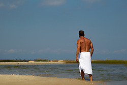 man in a white towel walking down the beach in East Hampton, NY