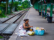 31 MAY 2017 - CHACHOENGSAO, THAILAND: A woman sets up her fruit stand on the platform at the train station in Chachoengsao, a provincial town about 50 miles and about an hour by train from Bangkok. The train from Chachoengsao to Bangkok takes a little over an hour but traffic on the roads is so bad that the same drive can take two to three hours. Thousands of Thais live outside of Bangkok and commute into the city for work on trains, busses and boats.       PHOTO BY JACK KURTZ