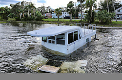 October 8, 2016 - Ormond-By-The-Sea, Florida, U.S. - A boat, sunk by high winds from Hurricane Matthew, sits on the shore of the Halifax River in Ormond-By-The-Sea. The Category 1 hurricane was dropping 8 to 20 inches of rain in the Tar Heel State and southeast Virginia. (Credit Image: © Joe Burbank/TNS via ZUMA Wire)
