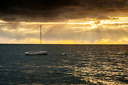A small sailboat rocks and rolls under  Wellfleet storm clouds and yellow rays of sunlight.