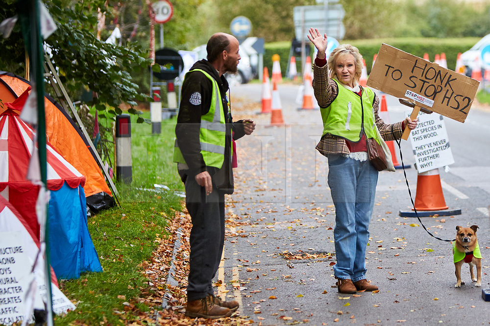 © Licensed to London News Pictures. 23/10/2019. GREAT MISSENDEN, UK.  Enabling works to allow the construction of the HS2 railway continue despite the future of the project being reviewed. A number of mature trees were due to be felled last week to allow easier access for construction traffic but local residents and climate activists created a makeshift camp to prevent their destruction. In this picture: Climate activist ALAN WOODWARD (centre) and ANN HAYWARD (left), with her dog Toby (12 year old Terrier cross) at the protest site. Photo credit: Cliff Hide/LNP