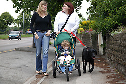 Women out walking with a baby in a buggy and a pet dog,
