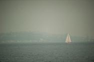 2018 AUGUST 20 - A sailboat on Elliott Bay as seen from near Don Armeni Boat Ramp as smoke fills the skies of Seattle, WA, USA. By Richard Walker