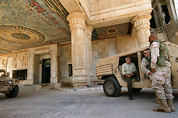Mowfaq Al-Tai, an Iraqi architect, is seen talking with two U.S. soldiers outside the now partially destroyed Salam Palace in Baghdad, Iraq, Sept. 29, 2003. The columns are a signature of Saddam's palaces, though there is no structural need for them. According to Al-Tai, the Salam Palace is most representative of the design and architecture used in the hundreds of palaces built for Saddam Hussein. Al-Tai was one the the engineers involved in the construction and quality control of the Hussein palaces.