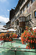Fountain with red flowers. Stein am Rhein has a well-preserved medieval center with beautiful frescoes, in Schaffhausen Canton, Switzerland, Europe.