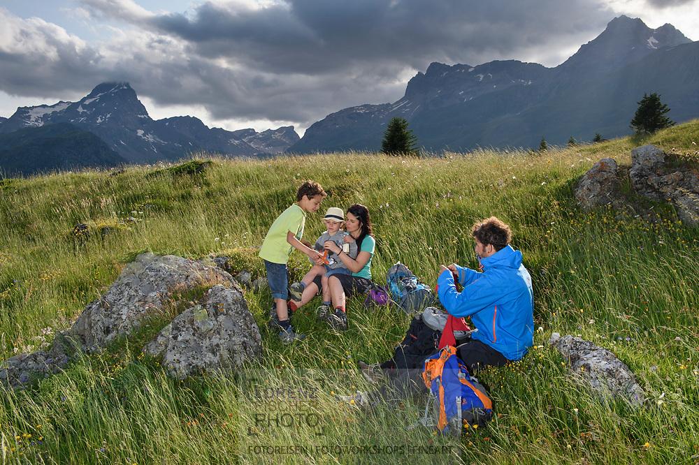 Eine Familie rastet auf der Alp Flix an einem schönen, bewölkten Sommertag mit den Piz Platta, Forbesch und Arblatsch im Blick, Parc Ela, Mittelbuenden, Schweiz<br /> <br /> Alp Flix on a nice, cloudy Summer day with Piz Platta, Forbesch and Arblatsch in sight, Parc Ela, Grisons, Switzerland
