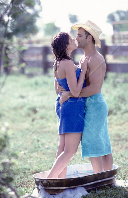 couple in an outdoor bathtub wrapped in towels embracing on a ranch