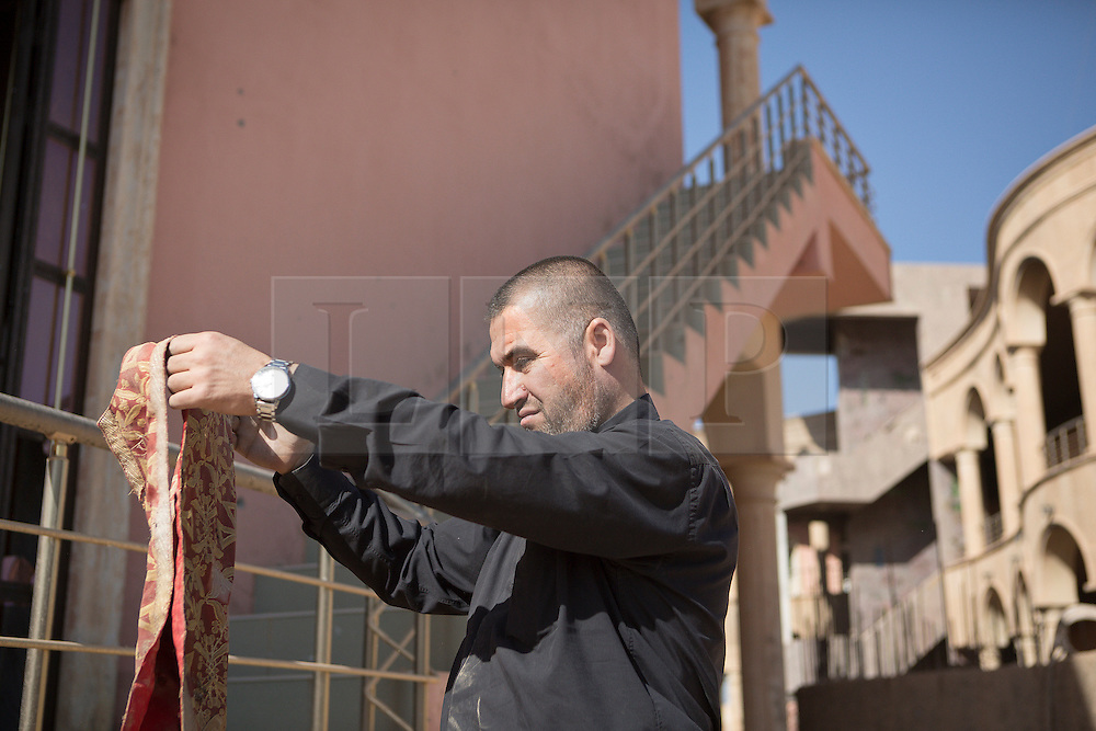 © Licensed to London News Pictures. 04/11/2016. Hamdaniyah, Iraq. Father Ignatius Offy, a Christian priest, examines a priest's stole, recovered from the Islamic State vandalised Christian academy in the town of Hamdaniyah, Iraq. Much of the academy was burnt, including its library, during the Islamic State's two year occupation of the town.<br /> <br /> Although located close to a front line, littered with improvised explosive devices and pieces of unexploded ordnance the Christian town of Hamdaniyah has only recently been cleared of ISIS extremists who stayed behind to fight. After the town's liberation as part of the Mosul Offensive residents and priests of the town are now free to take short trips to assess damage, salvage possessions and clear up the mess left by militants during their two year occupation.<br /> <br /> Hamdaniyah, and much of the Nineveh plains, were captured by the Islamic State during a large offensive on the 7th of August 2014 that saw the extremists advance to within 20km of the Iraqi Kurdish capital Erbil. Residents of the town, who included many Christian refugees who escaped there after the fall of Mosul, were then forced to seek sanctuary in the Kurdish areas. In the year and two months of the ISIS occupation churches were burnt, homes were put into use as militant accommodation and bomb factories and some buildings destroyed by coalition airstrikes. Photo credit: Matt Cetti-Roberts/LNP