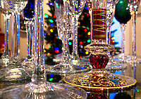 Champagne glasses sparkle in front of a Christmas tree.