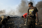 Boys rummage through ashes as they look for strings of copper wire near the Agbogboloshie market in Accra, Ghana on Thursday August 21, 2008.