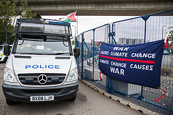 London, UK. 6 September, 2019. Metropolitan Police officers observe climate activists taking part in Stop The Arms Fair protests outside ExCel London on the fifth day of a week-long carnival of resistance against DSEI, the world's largest arms fair. The fifth day of protests was themed as Stop The Arms Fair: Stop Climate Change in order to highlight links between the fossil fuel and arms industries.