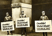 Anti-semitism in Germany, 1933. Nazi pickets outside a Jewish-owned store carrying placards which read 'Germans! Take Care! Do not buy from Jews!'.