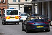 A Porsche convertible car drives behind a Metropolitan Police van on Stratton Street, central London, United Kingdom.