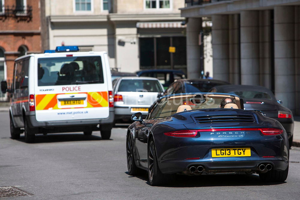 A Porsche convertible car drives behind a Metropolitan Police van on Stratton Street, central London, United Kingdom.