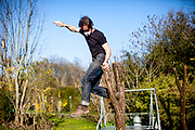 Portrait of a man with a mask jumping of a tree stump in times of social distancing related to the spreading of the corona virus.