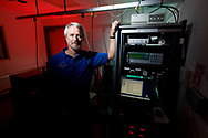 A scientist stands in front of an array of scientific equipment at the Mauna Loa Observatory, Hilo, Hawaii.