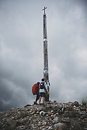 Pilgrims from Taiwan stand at the Cruz de Ferro, or Iron Cross, a landmark and, at 1530 meters, the highest point on the Camino Frances. Many pilgrims deposit a stone brought from home at the base of the cross. (July 1, 2018)<br />