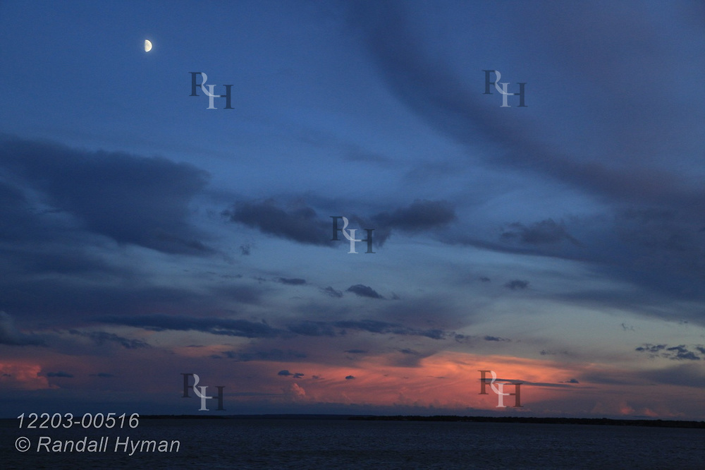 Half moon hangs above rosy clouds after sunset on Lake Huron's Thunder Bay; Alpena, Michigan.