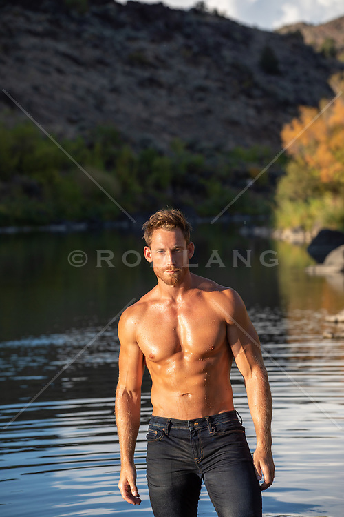 shirtless muscular man standing in a river in jeans at sunset