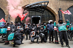 © Licensed to London News Pictures. 07/04/2021. LONDON, UK.  Deliveroo riders and drivers on strike stage a protest outside the company's headquarters in Cannon Street against the company demanding improvements to pay and conditions in terms of minimum wage, holidays and sick leave.  The strike comes on the same day that the company's shares are publicly traded for the first time following its initial public offering (IPO) on 31 March, where shares fell by 25% after failing to receive support by institutional investors who cited concerns about the company's policy on workers' rights.  Photo credit: Stephen Chung/LNP