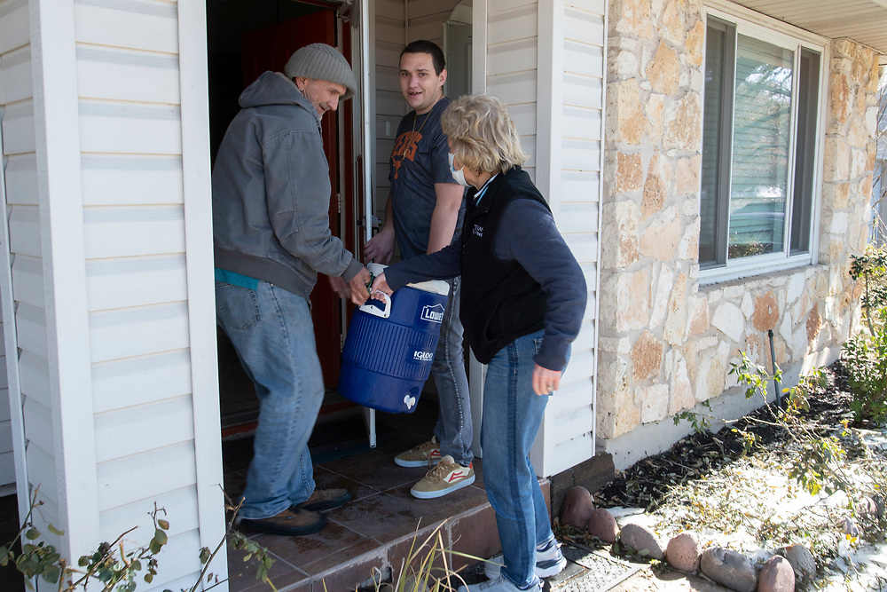 Austin, Texas USA Feb. 20, 2021: Ann Howard, r, helps two residents of a halfway house that are out of water in the Anderson Mill subdivision of north Austin during a water emergency in central Texas.  The are has been out of water for several days in the aftermath of a weeks long Texas storm aftermath.