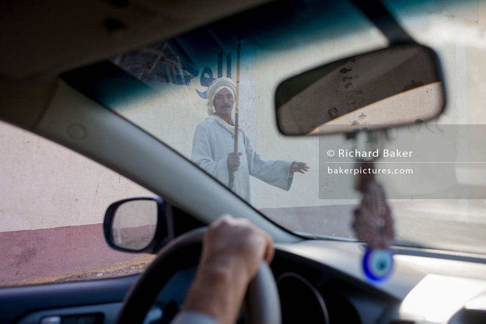 A traditionally-dressed villager seen through the windscreen of a modern car in the village of Qurna, on the West Bank of Luxor, Nile Valley, Egypt.
