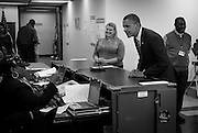 President Barack Obama leans in as a poll worker checks to make sure he matches his drivers license photo while voting in the Bronzeville neighborhood of Chicago on Thursday, Oct. 25, 2012.