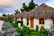 Boutique hotel cottages with thatched roof.