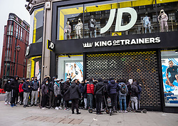Licensed to London News Pictures. 12/04/2021. London, UK. Members of the public queue outside JD sports clothing shop  in Oxford Street, London for the first time in months as pubs and shops across England open up and welcome customers back to their stores as the Covid-19 restrictions are lifted. Prime Minister Boris Johnson announced last week that non-essential shop, restaurants with outside seating , hairdressers and gyms can reopen today after 4 months of Covid-19 lockdowns. Photo credit: Alex Lentati/LNP
