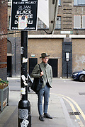 A fashionably dressed man on the streets of Shoreditch, London
