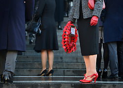© Licensed to London News Pictures. 11/11/2012. City of London, UK . A woman holds a poppy wreath. People arrive at a service of remembrance to remember those killed in action during conflict at St Pauls Cathedral, today 11 November 2012. Both Armistice Day and Remembrance Sunday fall of the same day this year. Photo credit : Stephen Simpson/LNP