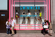 Shoppers in front of a window display featuring swimwear in Topshop's Oxford Street store in central London. Prominent pink rectangles dominate the landscape in front of this popular shop on London's busy shopping street in the capital's West End. Couples consult a map and the content on a phone on this warm midsummer day.