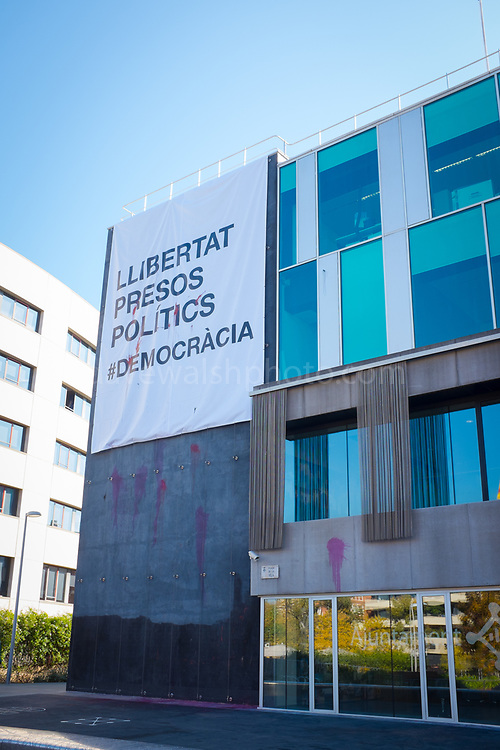"""Defaced poster on the town hall, or ajuntament of Sant Cugat del Valles, Barcelona. The poster, which replaces an earlier one torn down by far-right protestors, reads """"Liibertat Presos Politics"""" - Freedom for Political Prisoners in support of Catalan government ministers and civil society leaders jailed by Spanish government.  This version has been bombarded with paint bombs."""