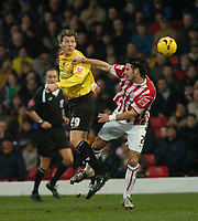 Photo: Leigh Quinnell.<br /> Watford v Stoke City. Coca Cola Championship.<br /> 14/01/2006. Watfords Darius Henderson rises above Stokes Carl Hoefkens.