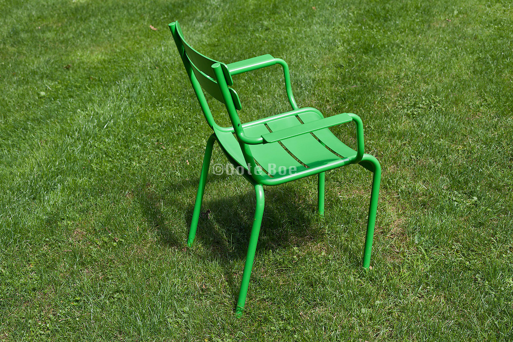 green outdoors chairs standing in a grass field