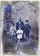father posing with his three young children early 1900s eroding glass plate photo