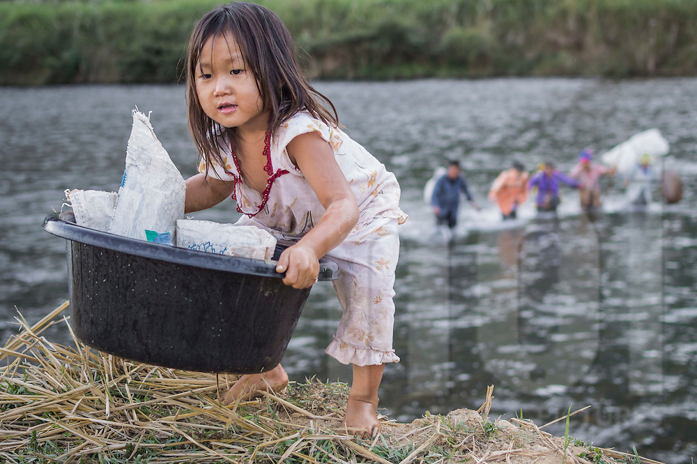 A little girl lifts up a bucket by the river near Vang Vieng in Laos, Southeast Asia