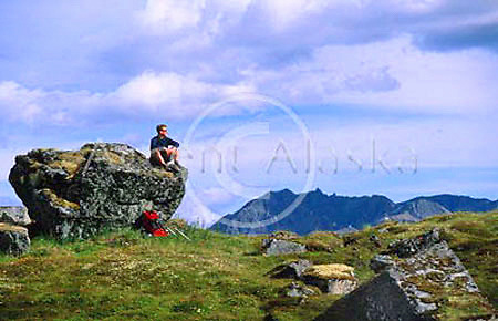 Alaska. Talkeetna Mountains. Hatchers Pass. Reed Lakes trail . Hiker relaxes and enjoys the view from above Reed Lakes.