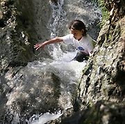 Young teen boy slides down a natural waterfall
