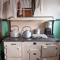 Vintage wool sweaters and long underwear hang above a coal-fired cookstove in the kitchen of a hut at Port Lockroy, an abandoned British Science base on Goudier Island, Antarctica that has been restored as a museum.