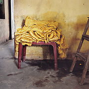 Piles of yellow silk on a plastic table at Dai Hung, a village specialising in producing silkworms and thread, Ha Tay province, Vietnam. With Vietnam's growing population making less land available for farmers to work, families unable to sustain themselves are turning to the creation of various products in rural areas.  These 'craft' villages specialise in a single product or activity, anything from palm leaf hats to incense sticks, or from noodle making to snake-catching. Some of these 'craft' villages date back hundreds of years, whilst others are a more recent response to enable rural farmers to earn much needed extra income.