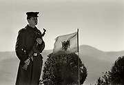"""Soldier in front of the Albanian flag guarding the statue of """"Mother Albania""""on the outskirts of Tirana is dedicated to the Partisans of WWII. On it is enscribed: Eternal Glory to the Martyrs of the Fatherland."""