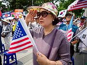 09 JUNE 2018 - SEOUL, SOUTH KOREA: A woman salutes while Hail to the Chief is played during a pro-American rally in downtown Seoul. Participants said they wanted to thank the US for supporting South Korea and they hope the US will continue to support South Korea. Many were also opposed to ongoing negotiations with North Korea because they don't think Kim Jong-un can be trusted to denuclearize or to not attack South Korea.    PHOTO BY JACK KURTZ